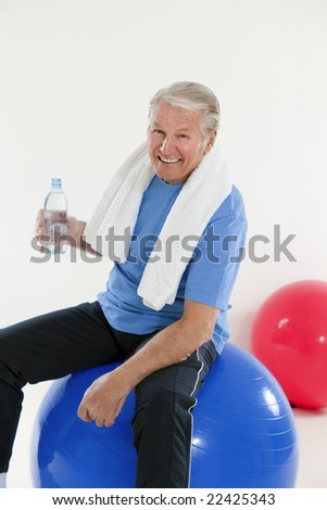 senior adult sitting on fitness ball in gym and holding water bottle