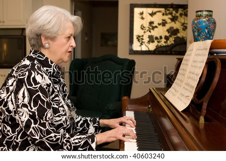 Senior adult woman in active retirement living plays the piano in her home.
