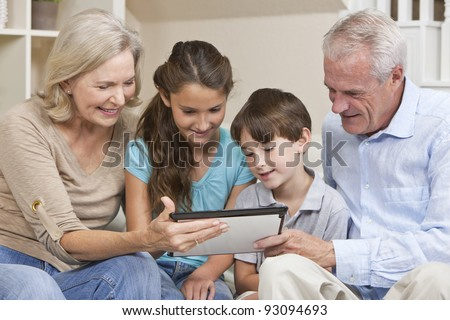 Senior adults and children, grandparents & grandchildren, sitting on a sofa at home having fun using a tablet computer