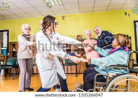 Senior adults in a nursing home for the elderly having fun and dancing