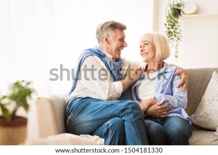 Senior affectionate couple relaxing and looking at each other on sofa at home