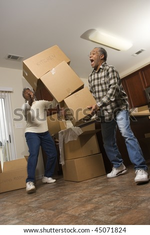 Senior african american man dropping stacked moving boxes while his wife attempts to catch them.