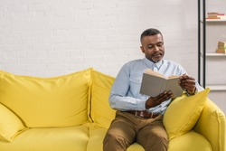 senior african american man sitting on sofa and reading book