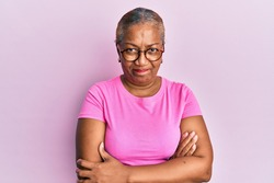 Senior african american woman wearing casual clothes and glasses skeptic and nervous, disapproving expression on face with crossed arms. negative person.