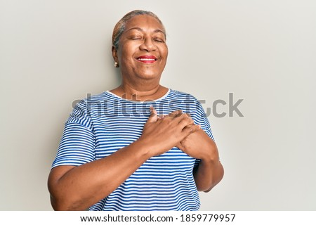 Senior african american woman wearing casual clothes smiling with hands on chest, eyes closed with grateful gesture on face. health concept.  Photo stock ©