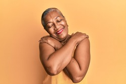 Senior african american woman wearing casual style with sleeveless shirt hugging oneself happy and positive, smiling confident. self love and self care