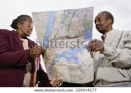 Senior African couple holding map
