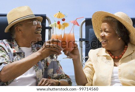 Senior African couple toasting with tropical cocktails - stock photo
