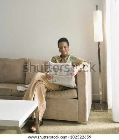 Senior African woman reading newspaper