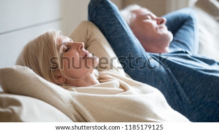 Senior aged couple relaxing on comfortable sofa together breathing fresh air at home, calm old mature man and woman enjoying no stress free weekend peaceful rest having healthy daytime nap on couch