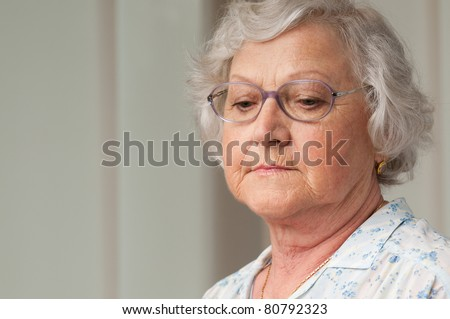 Senior aged woman looking down with sadness, indoor closeup shot