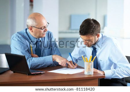 senior and junior businessman discuss something during their meeting, office background