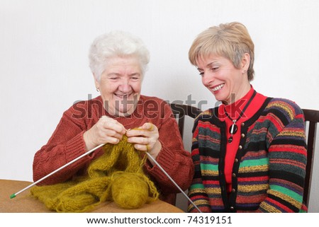 Senior and mature womans speaking  laughing  and learning knitting