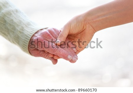 Senior and young holding hands over shiny white background
