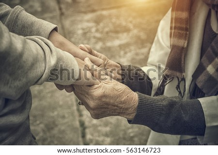 senior and young holding hands...