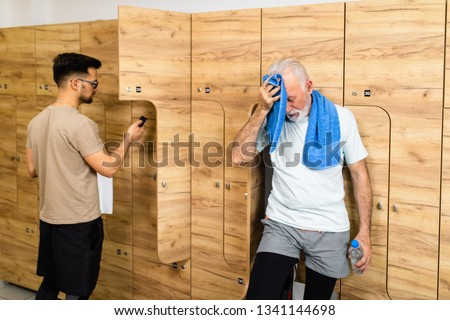 Senior and young sportsmen standing in the locker room after training at the gym.