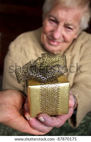 Senior and young women holding a gold gift box