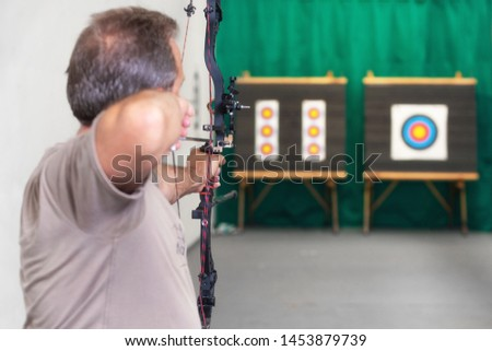 Senior Archer Training With The Bow. Shooting the target in the background . #1453879739