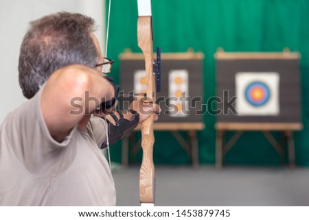 Senior Archer Training With The Bow. Shooting the target in the background . #1453879745
