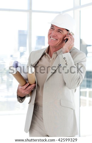 Senior architect on phone carrying blueprints in a building site