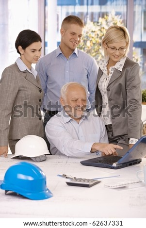 Senior architect showing work to businessteam on laptop computer, pointing at screen, smiling.?