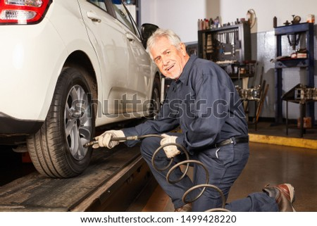 Senior as a car mechanic changing tires from winter tires to summer tires