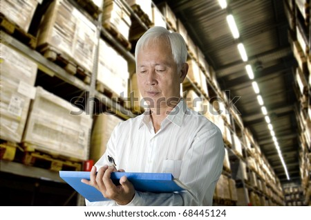 senior asian business man doing stock count in a warehouse