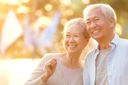 senior asian couple enjoying good time outdoors in park at dusk, happy and smiling