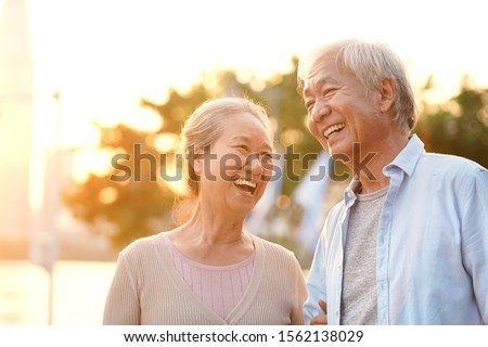 senior asian couple enjoying good time outdoors in park at dusk, happy and smiling Stockfoto ©