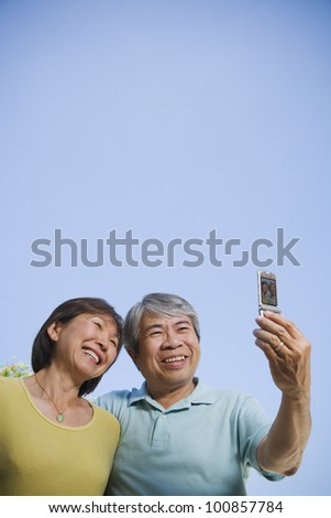 Senior Asian couple taking own photograph with cell phone