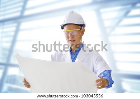 Senior Asian engineer with blueprints office background