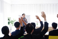 Senior Asian Lecturer is lecturing about business and stock market topics and business people are having a seminar and raising hands agree with teacher in the economics class in meeting room.
