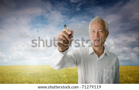 senior asian man drawing with blank space for any text purpose , focus on pen and hand