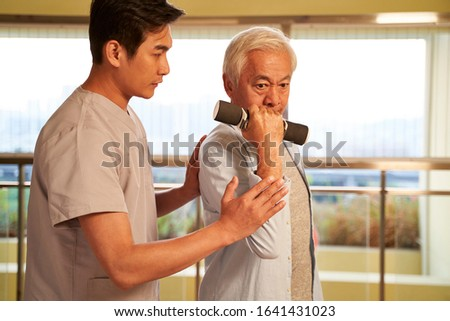 senior asian man exercising using dumbbells guided by physical therapist in rehabilitation center