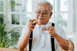 Senior Asian man with cup of water and pill taking remedy in cozy room at home. Old male taking medicine