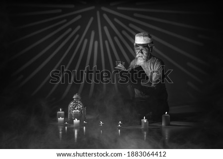 senior asian muslim man with gray beard holding muslim rosary bead  and holy al kuran book with written arabic calligraphy meaning of Al Quran reading al quran book in black and white Stok fotoğraf ©