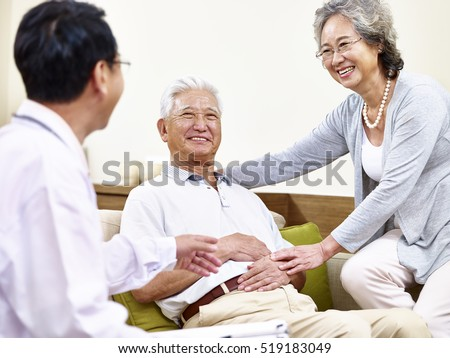 senior asian patient being taken care of by his wife and a family doctor