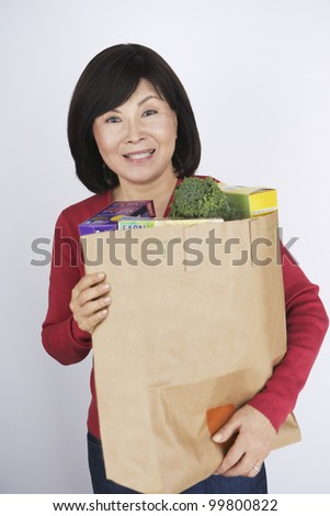 Senior Asian woman carrying grocery bag