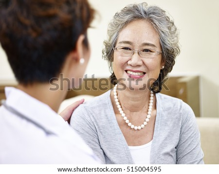 senior asian woman having a pleasant conversation with her family doctor, happy and smiling #515004595
