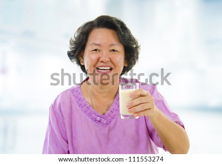 Senior Asian woman holding a glass of soy milk at home
