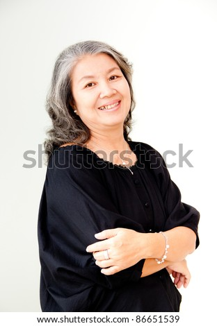 senior asian woman smiling with arms folded