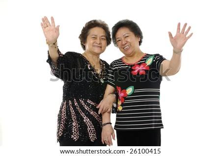 senior asian woman waving and saying hallo