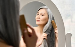 Senior attractive middle 50 years aged asian woman with gray hair looking at mirror reflection combing tangled gray hair. Alopecia hair loss prevention treatment after menopause advertising concept.