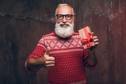 Senior bearded man holding gift box over dark background and looking at camera with smile and gestures thumbs up. Santa Claus wishes Merry Christmas and a happy new year 2018!