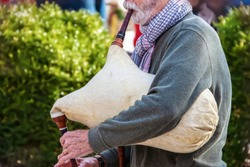 Senior bearded man is sweater and scarf playing old sheepskin bagpipe outdoors - cropped and selective focus