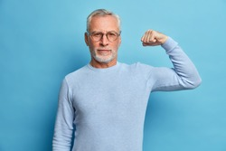 Senior bearded man shows muscles after practising bodybuilding wears transparent glasses and basic jumper poses against blue studio background. Look I am very strong and healthy. Perfect biceps