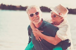 senior beautiful couple outdoor at the beach enjoying vacation and leisure. together life with joy having fun the man carry the woman on his back. summer time and vacation