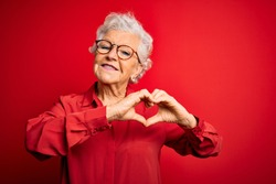 Senior beautiful grey-haired woman wearing casual shirt and glasses over red background smiling in love doing heart symbol shape with hands. Romantic concept.