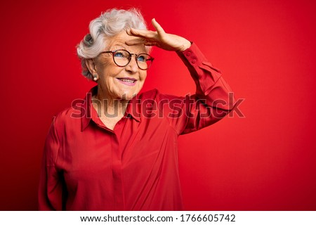 Photo of  Senior beautiful grey-haired woman wearing casual shirt and glasses over red background very happy and smiling looking far away with hand over head. Searching concept.