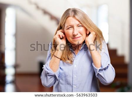 senior beautiful woman covering ears